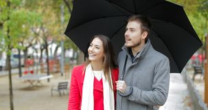 Couple walking and pointing away under the rain stock video footage