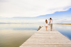 Couple walking and pointing to the horizon. Back view of men and women couple walking and pointing to the horizon under a blue cloudy sky Stock Photo