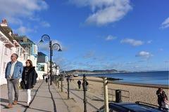 Couple walking on promenade in sea town . Royalty Free Stock Photos