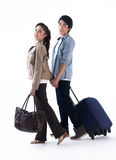 A couple walking and pulling luggage. Young couple walking hand in hand and pulling a luggage Royalty Free Stock Photo