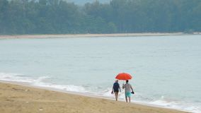 Couple walking on the beach. Couple walking in the rain on the beach, Nai Yang beach, Phuket, Thailand stock footage