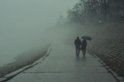 Couple walking beside river on misty winter day Royalty Free Stock Photo