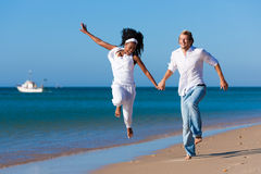 Couple walking and running on beach stock images