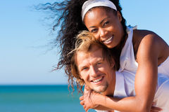 Couple walking and running on beach. Couple in love - Caucasian man having his African-American woman piggyback on his back under a blue sky on a beach Royalty Free Stock Photography
