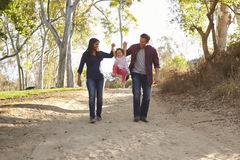 Couple walking on rural path lifting daughter, full length stock images