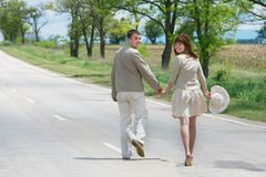 Couple walking by rural road Stock Images