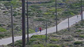 Couple Walking With Running Children On Rural Road. Couple Walking On A Rural Road With Two Young Boys Running And Chasing Each Other stock video footage