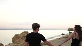 Couple walking on the sand beach stock video footage