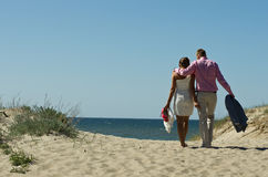 Couple walking on sand dunes. Affectionate couple casually dressed walking on the sand dunes towards the sea royalty free stock photos