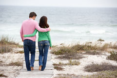 Couple walking by the sea. Arms round eachother stock photography