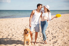 Couple walking on the sea shore with dog Royalty Free Stock Photos