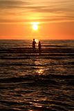 A couple walking in the sea during sunset Stock Photos