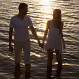 Couple walking by the sea at sunset Stock Photography