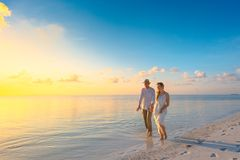 Couple Walking on Seashore Wearing White Tops during Sunset Stock Image