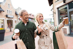 Couple walking with shopping bags and drinking coffee on street Stock Images