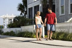 Couple walking on sidewalk. Stock Photo