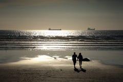 Couple walking on a silhouette sunset beach Stock Photos