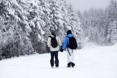 Couple walking on snow covered path Stock Photo