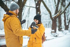 Couple walking by snowed city park talking socializing. romantic date in winter time stock photos