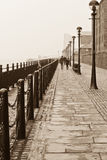 Couple walking. A couple stroll along the pierhead at Liverpools Albert dock Stock Image