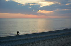 Couple walking in sunset. Couple walking on beach with sunset Stock Images