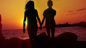Couple walking at sunset on the beach. HD: Romantic Walk - Stock Video. HD1080: Boy and girl as a silhouette are taking a walk on a wonderful evening (morning) stock video footage