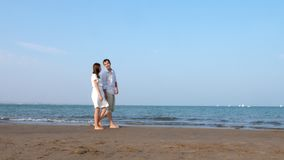 Couple walking at sunset beach romantic embracing. holding hands near the shore.  stock footage