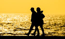 Couple walking sunset silhouette Stock Photos