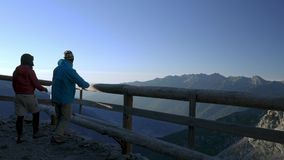 Couple walking to wooden balcony and looking at mountain view at sunrise high up on the Alps.  stock video