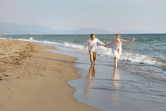 Couple walking together holding hands on the beach near sea Royalty Free Stock Photo