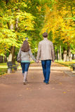 Couple walking together in park on a fall day Royalty Free Stock Images