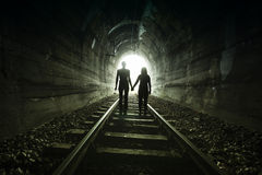 Couple walking together through a railway tunnel Royalty Free Stock Image