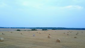 Couple Relaxing On A Field With Hay Bales stock video footage
