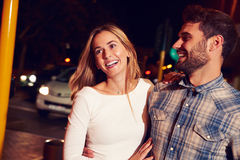Couple walking through town together at night Royalty Free Stock Photos