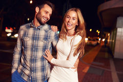Couple walking through town together at night Royalty Free Stock Photo