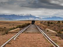 Couple walking on the train tracks in the steppe of Patagonia. Argentina royalty free stock photos