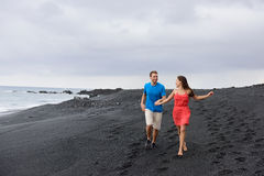 Couple walking travel holidays black sand beach. Couple walking during travel holidays on secluded black sand beach. Full length shot of people in love running stock photography