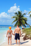 Couple walking on tropical beach. Man and woman walking along white sandy tropical beach Royalty Free Stock Photos