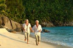 Couple walking on  tropical beach. Happy elderly couple walking on  tropical beach Stock Photos