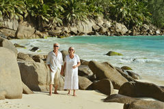 Couple walking    at tropical beach. Happy elderly couple walking    at tropical beach Royalty Free Stock Image