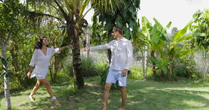 Couple Walking In Tropical Garden Holding Hands Talking, Happy Man And Woman Outdoors. Couple Walking Holding Hands In Tropical Garden Talking, Happy Man And stock video footage