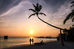 Couple Walking on Maldivian Island Resort Beach at Sunset stock images