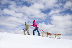 Couple walking up ski slope pulling sled Royalty Free Stock Photos