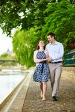 Couple is walking by the water in Paris Royalty Free Stock Image