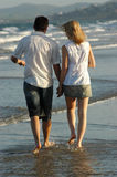Couple walking on waters edge at beach stock photos