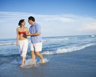 Couple walking in waves. stock photography