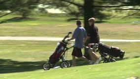 Couple walking with wheeled golf bag (1 of 2)