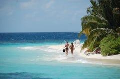 Couple walking at white sand beach Maldives Stock Photography