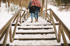Couple walking winter park under american flag style cloth Royalty Free Stock Photography