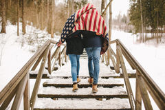 Couple walking winter park under american flag style cloth Royalty Free Stock Photo